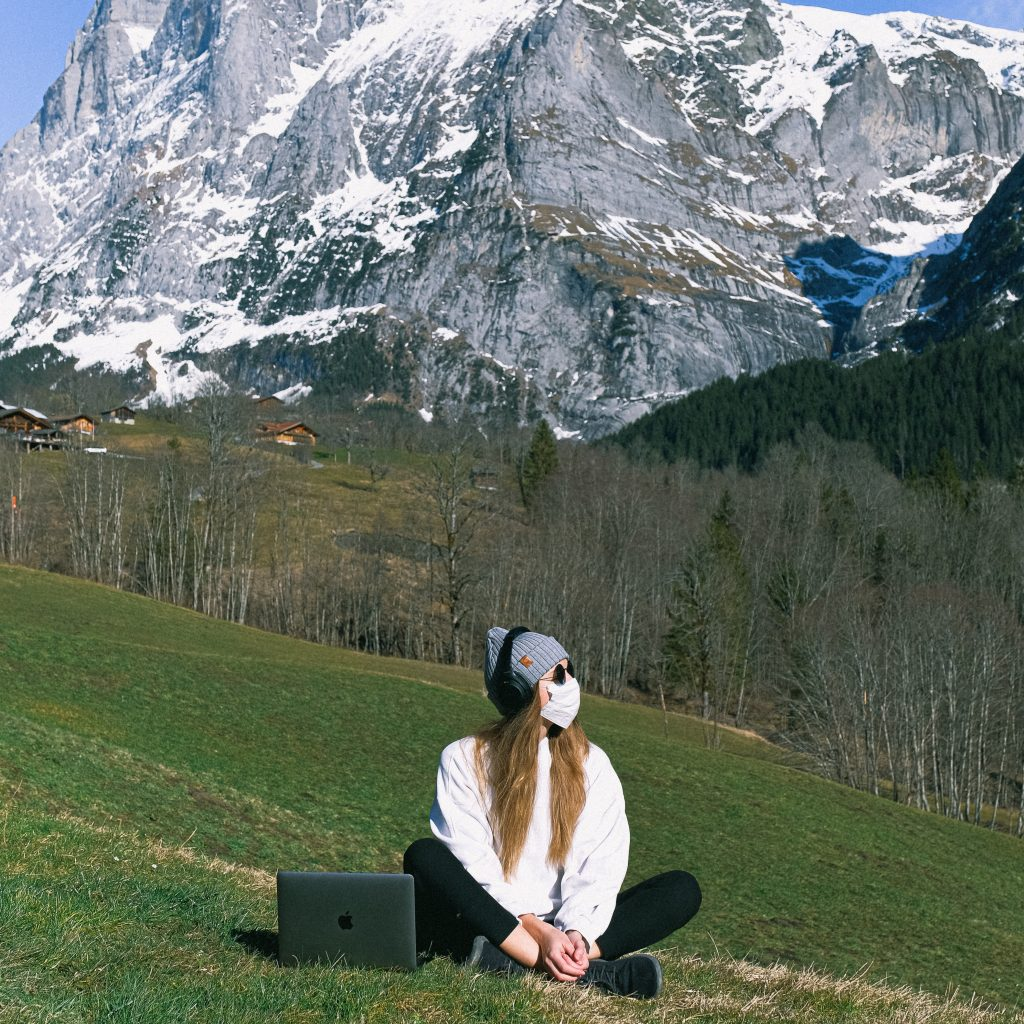 girl with mask doing chakra meditation by snowcapped mountains